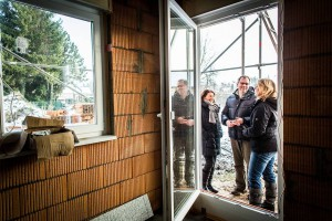 Nach Fertigstellung der Dachkonstruktion erfolgt der Einbau von Fenstern und Haustür. Bauherrenberaterin Giertz begutachtet die Anschlüsse im Bereich der Fensterlaibung und Rollladenkästen, prüft die Winkelverankerung der Türen auf dem Rohfußboden und die Qualität der Montage der Fensterbänke. Vom Ergebnis wird der Bauherr in Kenntnis gesetzt. Quelle: BSB e.V.