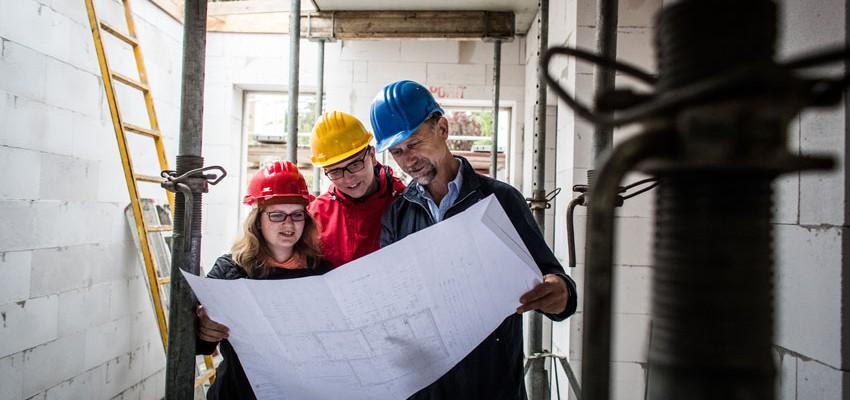 Bevor der Kontrollgang beginnt, werfen Bauherren und Bauherrenberater noch einen Blick auf die Bauzeichnung. Der Erdgeschossrohbau lässt die künftige Raumlandschaft erkennen.