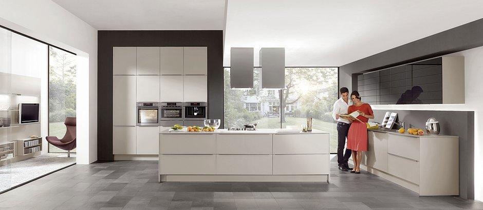 Offene Lifestyle-Wohnküche mit einer horizontal betonten Linienführung, die sich im Arrangement der Einbaugeräte fortsetzt. Unter dem Kaffeevollautomaten und Dampfgarer befinden sich je eine Wärmeschublade. (Foto: AMK)