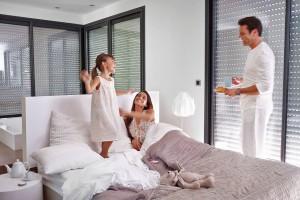 Während die Sonne langsam sichtbar wird, öffnen sich die Rollläden bis zur Hälfte und lassen sanft gedämpftes Morgenlicht ins Schlafzimmer fallen.