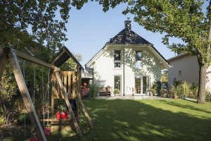 """Ein wahres Spielparadies für die Kinder ist der Garten. Auf dem geschützten Freisitz auf der Terrasse kann die Familie ihr """"Wohnzimmer im Grünen"""" genießen. Foto: Roth-Massivhaus / Gerhard Zwickert"""
