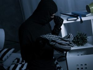 Maskierter Einbrecher hält eine Taschenlampe © Photographee.eu / Fotolia.com