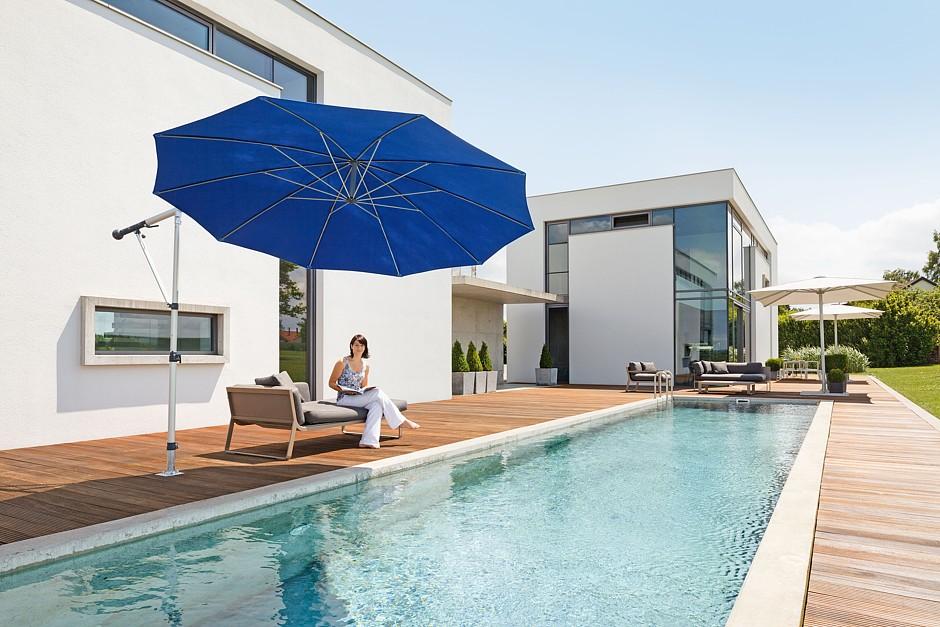 So lässt sich die Sommersonne aushalten: Gut geschützt unter einem seitlich gehaltenen Schirm, der sich leicht verstellen lässt. Foto: djd/May Gerätebau GmbH