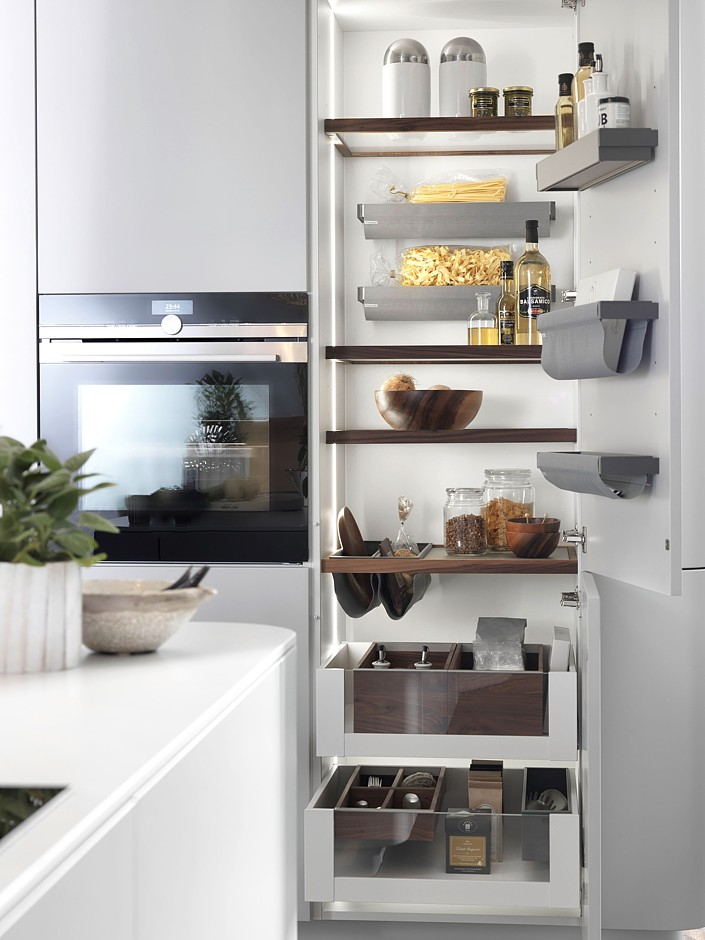 Ein besonderer Blickfang ist die beleuchtete Innenausstattung dieses Hochschranks – eine Kombination aus gerahmten Glasböden, multifunktionalen Holz-Einlegeböden mit Ausschnitt und herausziehbaren Schubladen. (Foto: AMK)