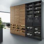 Die Küchen werden gemütlicher und wachsen mit dem Wohnzimmer zusammen. Dabei spielen auch dunkle Töne in der Kombination mit Holzoptik eine große Rolle. (Foto: AMK)