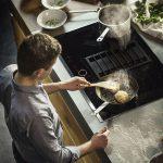 Die der Funktionen des Kochfelds und die Effizienz eines Dunstabzugs in einem Gerät bedeutet ein Plus an Flexibilität mit Kopffreiheit. Der Abzug ist direkt in das Kochfeld integriert, sodass der Platz in der Küche optimal genutzt wird. Der gusseiserne Rost in der Mitte kann zwischendurch auch als schnelle Abstellfläche für schwere Pfannen und Töpfe genutzt werden. (Foto: AMK)