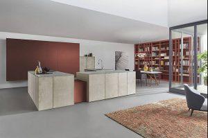 Farbe in der Küche: Aufmerksamkeitsstark und sehr präsent ist diese Premium-Designküche in dem erdigen, tief leuchtenden Farbton Rotocker und hellen, von Hand aufgetragenen Oberflächen, die wie echter Sandstein wirken. © AMK