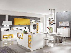 Farbe in der Küche: Eine Portion Sommerfeeling zaubert diese attraktive Wohnküche in Sonnengelb und Weiß in jeden Alltag. Durch die integrierte Regalbeleuchtung kommen die Farbakzente so richtig zum Strahlen.