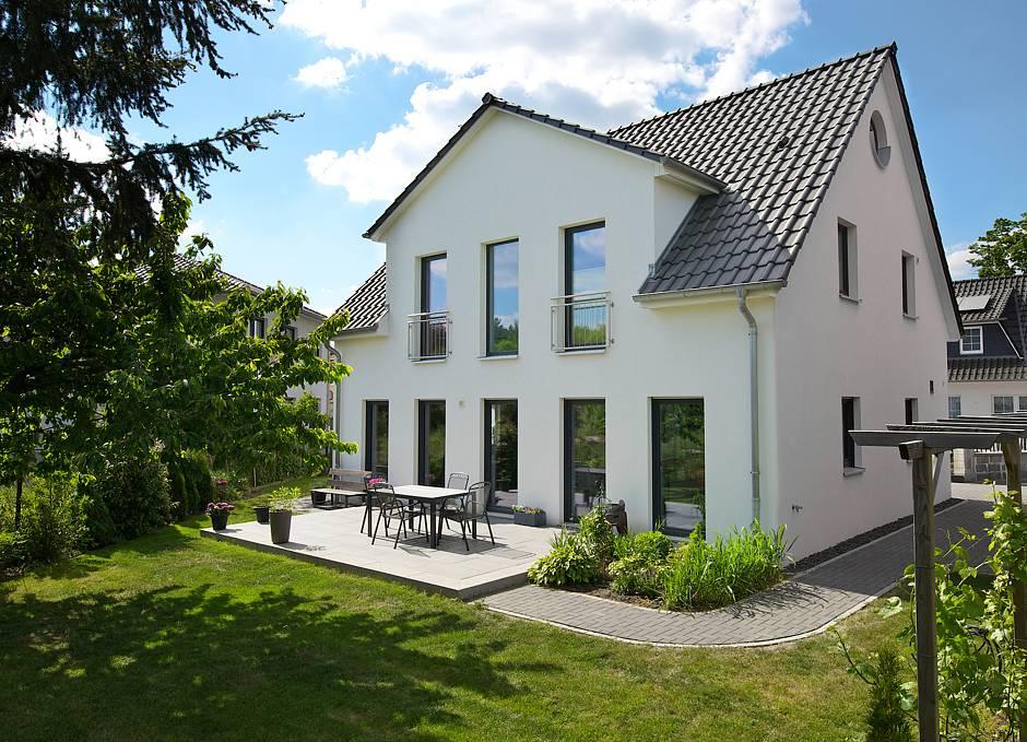 Blick vom Garten auf Terrasse und Rückseite des anderthalbgeschossigen Gebäudes. Bo-dentiefe Fenster erweitern den Wohnbereich ins Grüne. Fotos: HELMA Eigenheimbau AG / Christoph Große