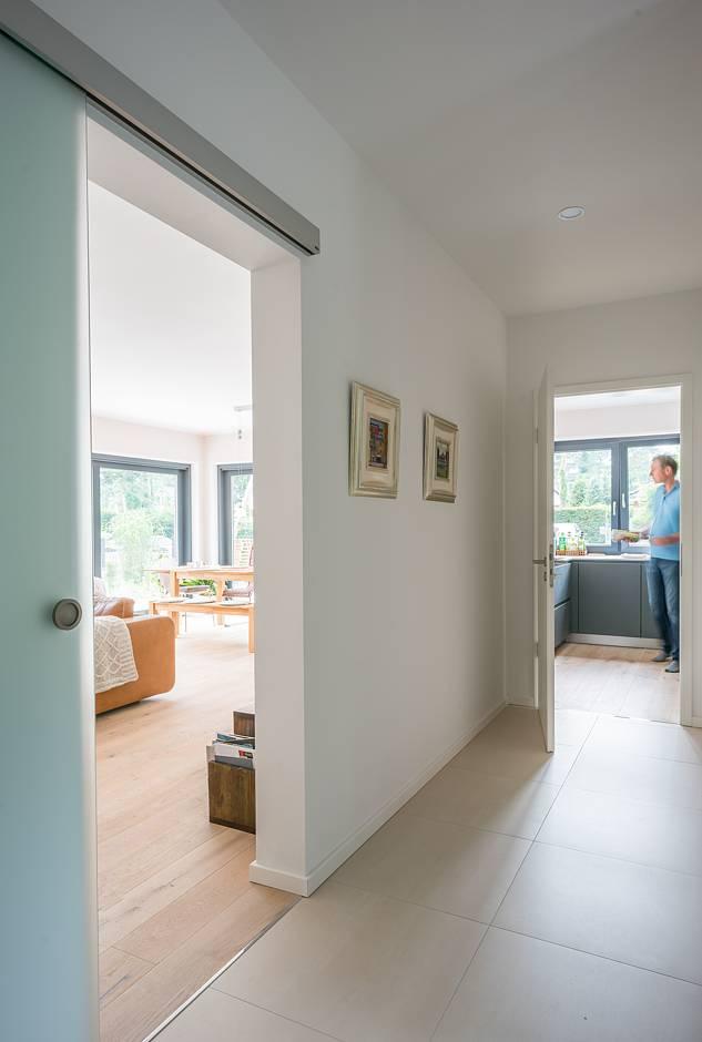 Die Glasschiebetür zum Wohnbereich lässt viel Licht in den Flur Foto: maasgestaltet