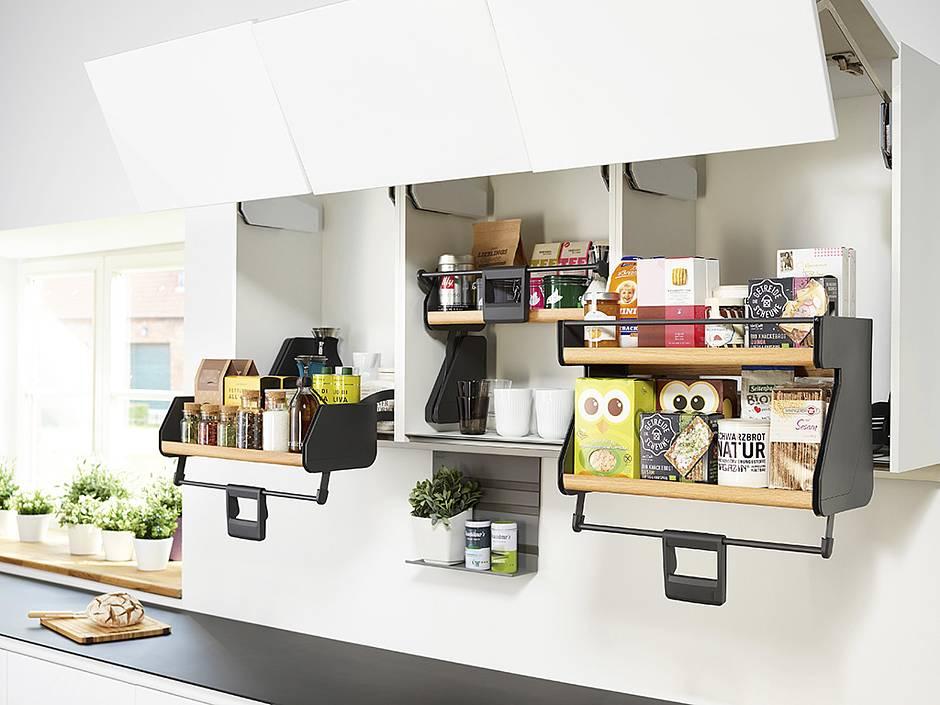 Für Mehrwert in der Küche sorgen z. B. Hängeschränke, die mit einem intelligenten Auszugssystem – wie diesem ergonomisch absenkbaren Doppeltablar – ausgestattet sind. Auf sanften Zug hin kommt das Staugut komfortabel entgegen. Foto: AMK