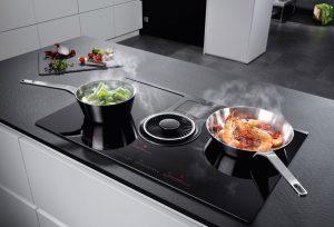 Kochen & lüften in einem: Bei dieser innovativen 2in1-Lösung ist der Dunstabzug direkt ins Induktionskochfeld integriert, sodass die kompakte Einheit in einer neuen offenen Wohnküche an jeder gewünschten Position eingebaut werden kann. Foto: AMK