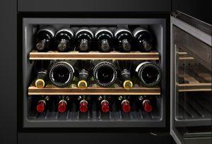 Dieser energieeffiziente Einbau-Weinklimaschrank mit pflegeleichten Oberflächen in Schwarzglas und Edelstahl bietet Platz für bis zu 18 Flaschen. Die perfekte Ergänzung findet er in einer intelligent durchdachten Sommelier-Schublade. Foto: AMK