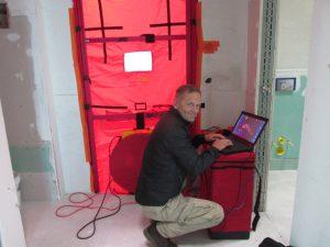 Bausachverständiger Andreas Lindner beim Luftdichtigkeitstest. © DEKRA