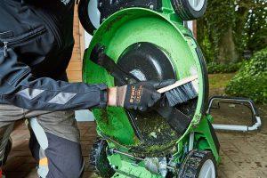 Auch die Unterseite des Rasenmähers will nach dem letzten Einsatz der Saison gründlich gesäubert werden. Foto: djd/Viking