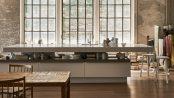Wohnküchen – lebenssprühend sinnanregend. Die Kücheninsel fasziniert durch Kontraste: ein symmetrisch-asymmetrisches Design sowie geschlossene und offene Bereiche mit ausziehbaren Holztablaren. Foto: AMK