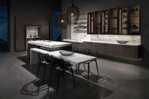 Diese Lifestyle-Wohnküche mutet luxuriös und geheimnisvoll an. Das dunkle Holzdekor weist ein interessantes Farbspiel auf – je nach Blickwinkel zwischen schwarz und dunkelgrau. Die perfekte Ergänzung dazu: ein Umfeld in weißem Marmor. Foto: AMK