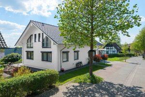 Die weiß gestrichen Hauswände stehen in spannendem Kontrast zum Satteldach, den Fensterrahmen und Rollladenkästen, welche in Anthrazit gehalten sind. © Fullwood Wohnblockhaus