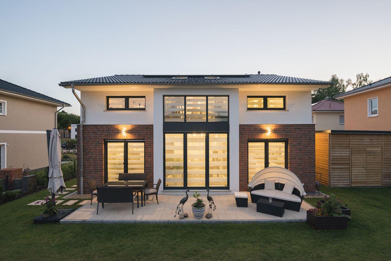In der Dämmerung strahlt die Fenstersymmetrie stilvolle Eleganz. Terrasse und Garten laden zum Entspannen ein. Foto: Roth-Massivhaus / Gerhard Zwickert