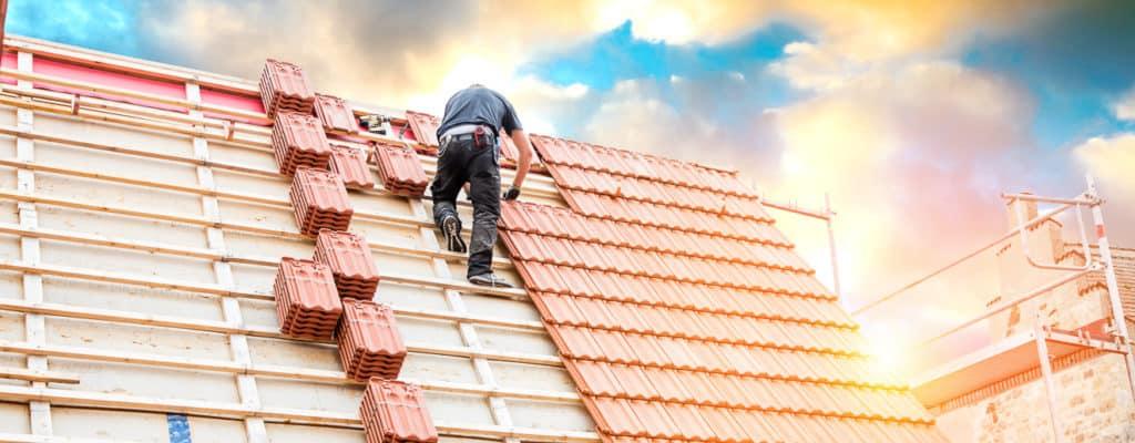 Dachdecker auf einem Spitzdach beim Dachdecken Foto: ©karepa - stock.adobe.com