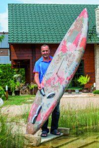 Swen Schützler mit seinem in den 80-ern selbst gebauten Surfbrett. Foto: © uwe weiser / FULLWOOD Wohnblockhaus