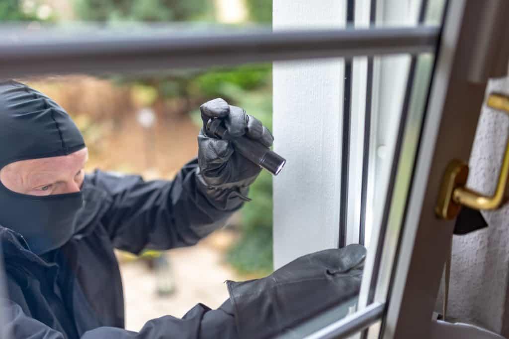 Einbrecher will mit einer Brechstange ein Fenster aufhebeln