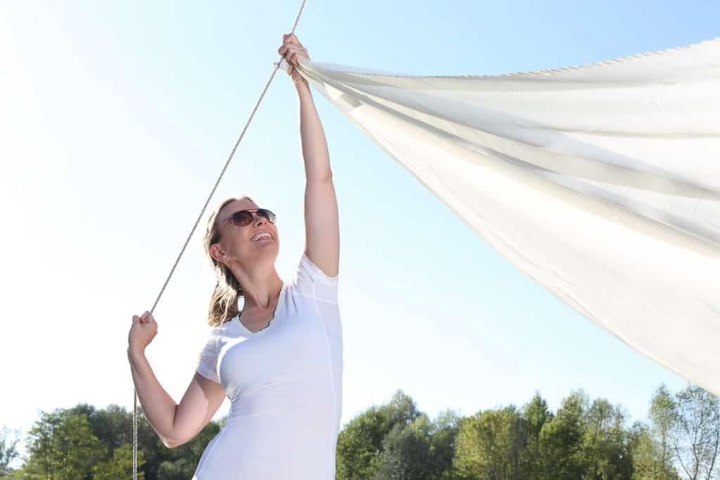 Frau beim Anbringen einen Sonnensegels