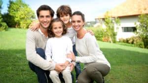 Glückliche Familien vor ihrem Haus