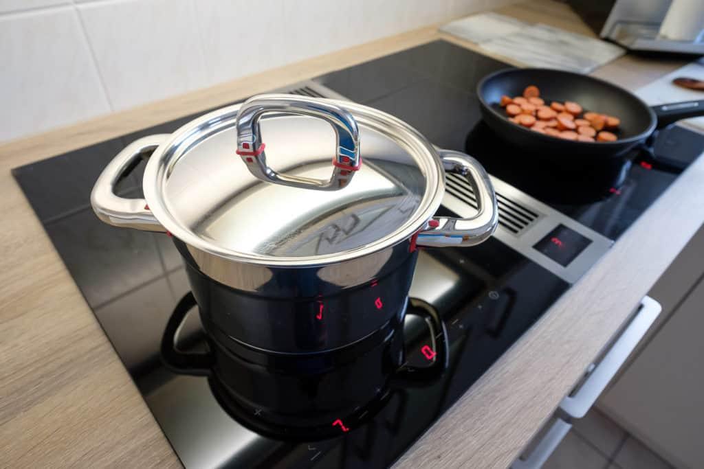 Kochtopf und Deckel aus Chrome auf einem Kochfeld mit Dunstabzug