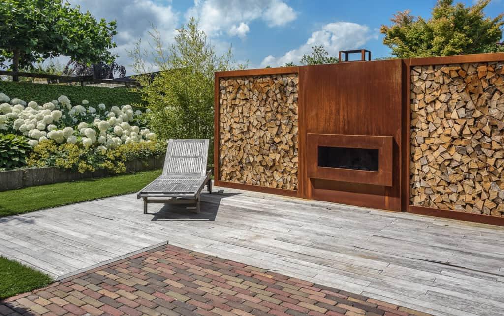 Outdoorkamin mit Holzstapel als Sichtschutz für die Terrasse