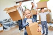 Mädchen hilft den Eltern beim Tragen der Umzugskartons ins neue Eigenheim in Berlin
