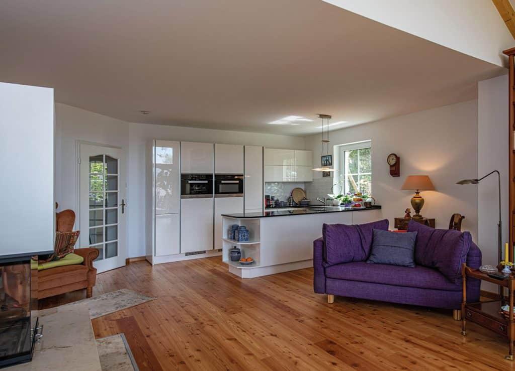 Blick in den Wohnbereich und auf die moderne Küche mit freistehendem Küchenblock. © Roth-Massivhaus / Claudius Pflug