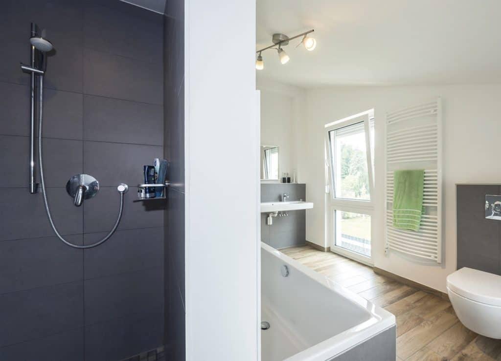 Hell und großzügig: Das Bad mit bodengleicher Dusche, Wanne und zwei Waschbecken. Dank des zusätzlichen kleinen Duschbads im Erdgeschoss gibt es morgens keinen Stau vor der Badezimmertür. Foto: Bau-GmbH Roth