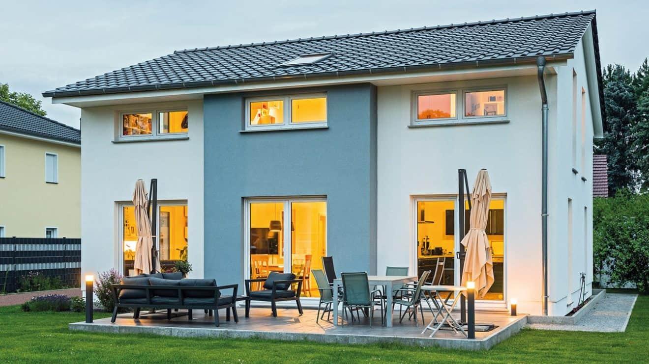 Dieses Haus Hamburg im Berliner Umland macht schon von außen Lust auf mehr: Die klar gegliederte Fassade in elegantem Weiß und Anthrazitgrau öffnet sich zu Terrasse und Garten mit großen, bodentiefen Fenstern. Foto: Bau-GmbH Roth