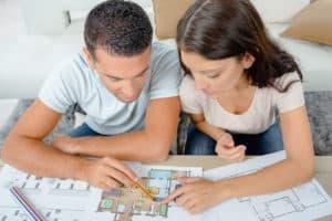 Junge Paar schaut sich Hausbaukatalog an