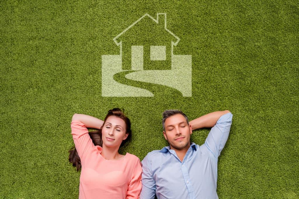 Junges Paar liegt auf einem Grundstück und träumt vom eigenen Haus