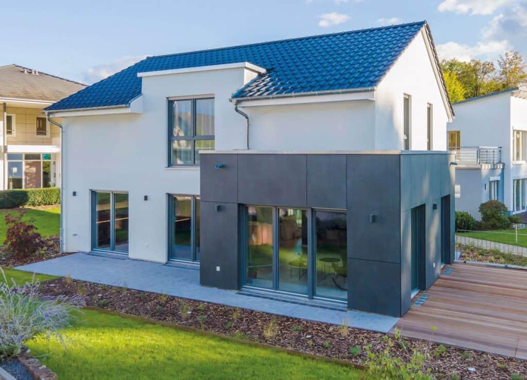 Anthrazitfarbene Fassadenplatten unterstreichen die schlicht-elegante Wirkung. Eine Flachdachgaube auf der Gartenseite bringt zusätzliches Licht in das Obergeschoss. © Helma Eigenheimbau AG / Emiliyan Frenchev