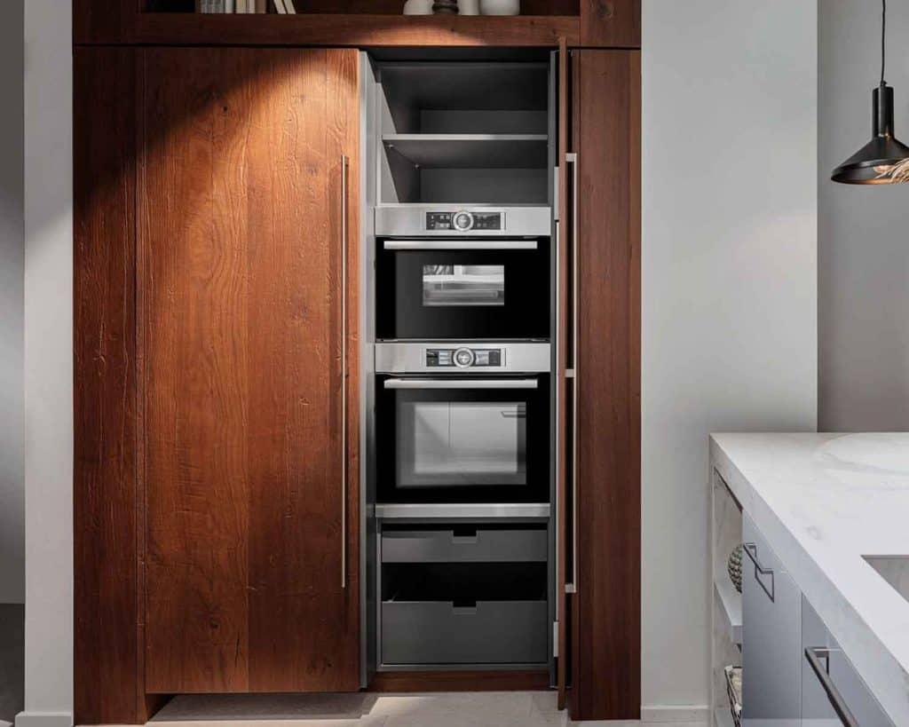Sesam, öffne Dich! Bei sogenannten Pocket-Door-Schränken werden die Türen nach dem Öffnen seitlich in den Korpus eingeschoben, sodass sie beim Benutzen der Geräte nicht im Weg sind. Und nach Feierabend ist die Küchentechnik im Nu wieder unsichtbar. © AMK